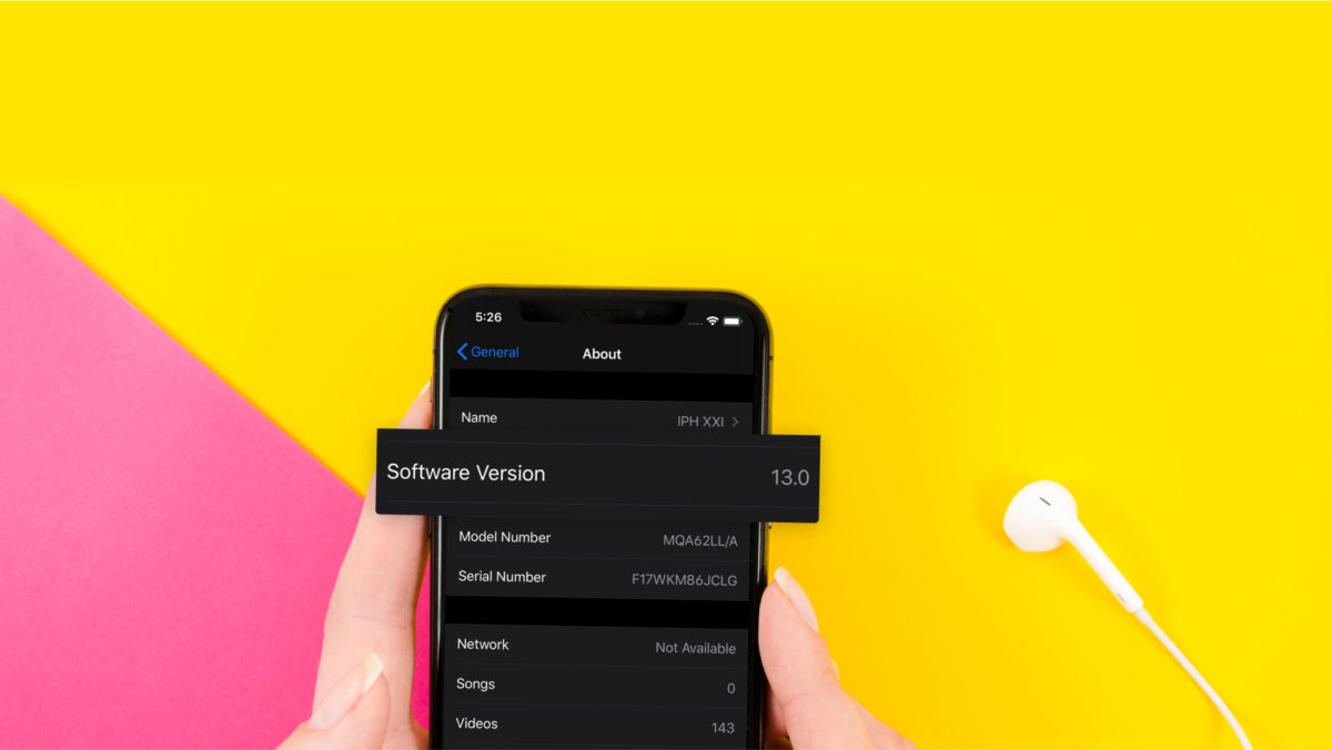 Someone holds an iPhone with iOS 13 and dark mode enabled